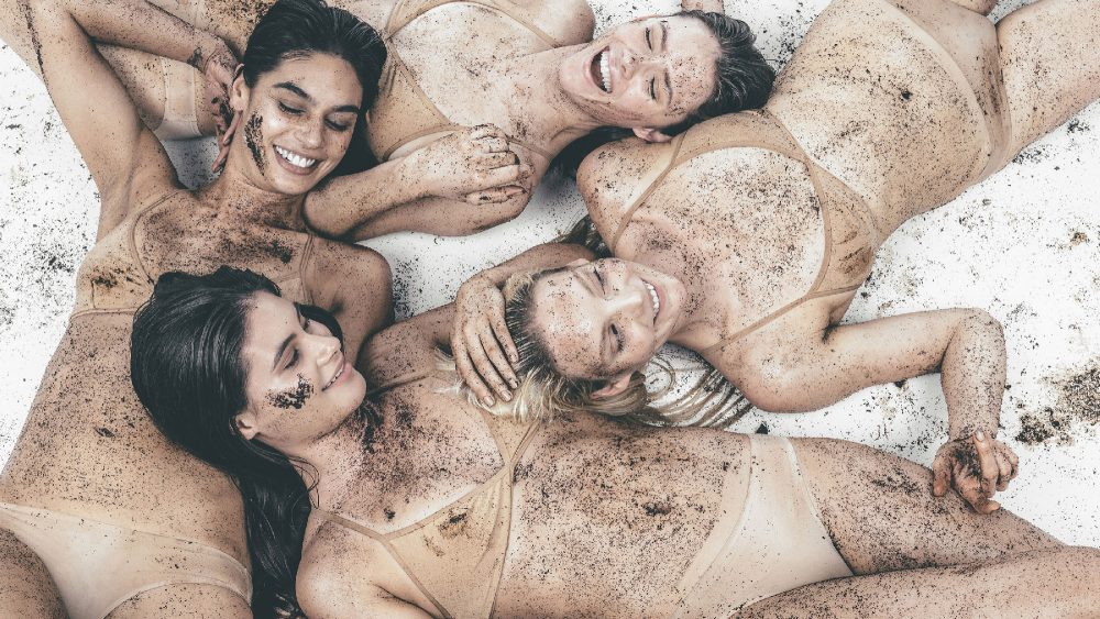 girls laying down on the ground covered in frank body coffee scrub
